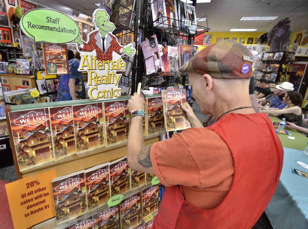 Ralph Matthieu, owner of Alternate Reality Comics, restocks the rack during a book launch and signing for ÒWhere We Live,Ó a comic book anthology dealing with the Route 91 Harvest Festiv ...