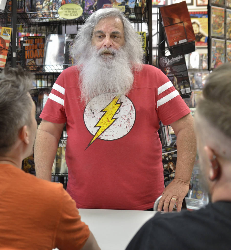 "Randy Simon, center, talks with ""Where We Live"" contributors Matt Sorvillo, left, and Josh Ellis during a book launch and signing for the comic book at Alternate Reality Comics at 4110 S ..."
