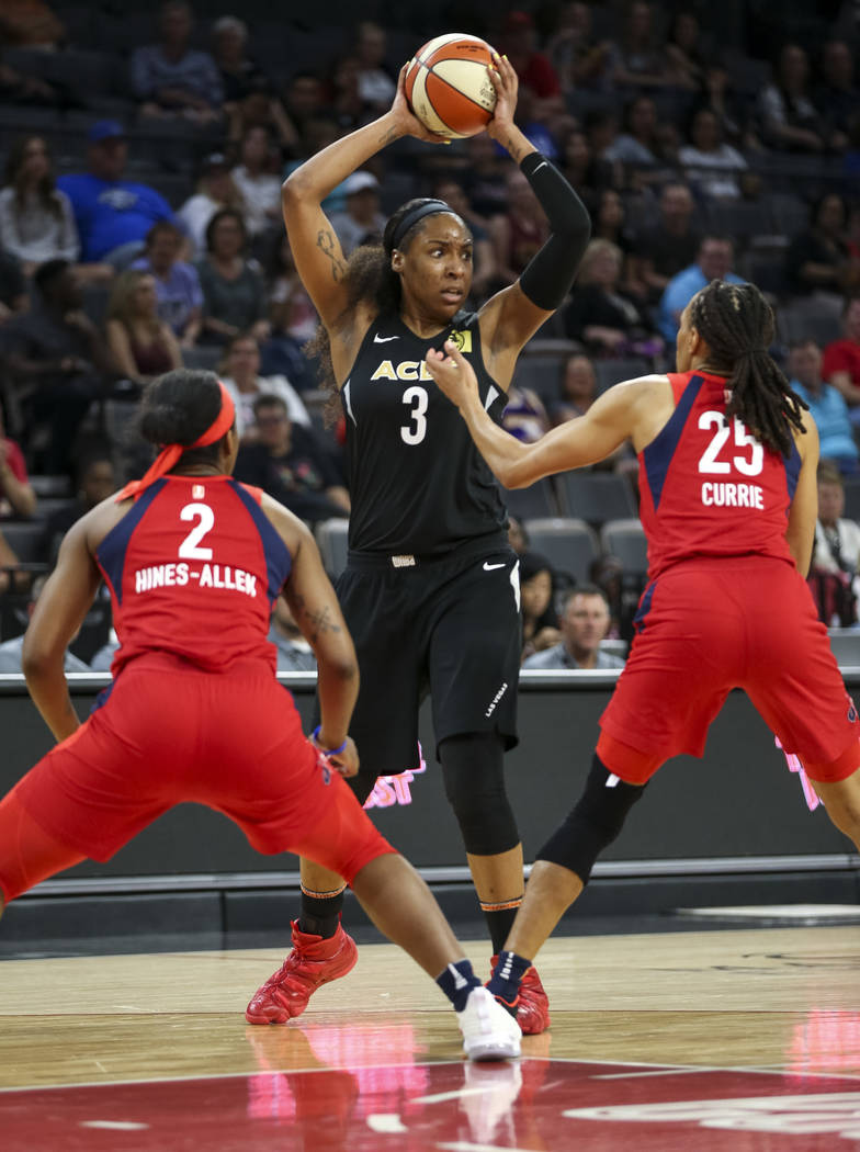 Las Vegas Aces center Kelsey Bone (3) looks to pass against Washington Mystics forwards Myisha Hines-Allen (2) and Monique Currie (25) in the second half of a WNBA basketball game at the Mandalay ...