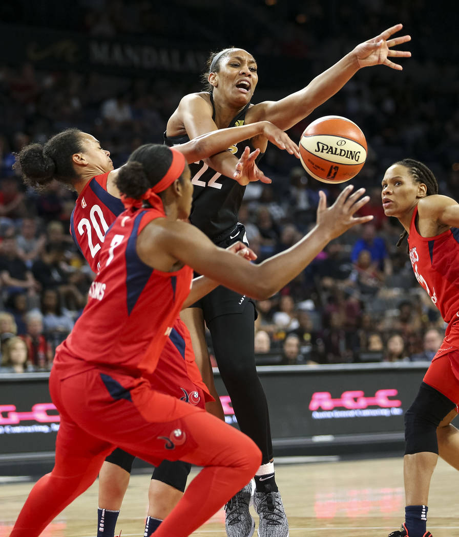 Las Vegas Aces center A'ja Wilson (22) loses the ball and gets fouled by Washington Mystics forward Monique Currie, right, as Mystics guards Kristi Toliver (20) and Ariel Atkins (7) defend in the ...