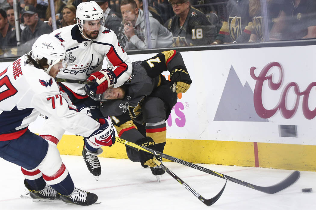 Washington Capitals defenseman Matt Niskanen (2) pushes Golden Knights center William Karlsson (71) as Washington Capitals right wing T.J. Oshie (77) goes for the puck during the third period of G ...