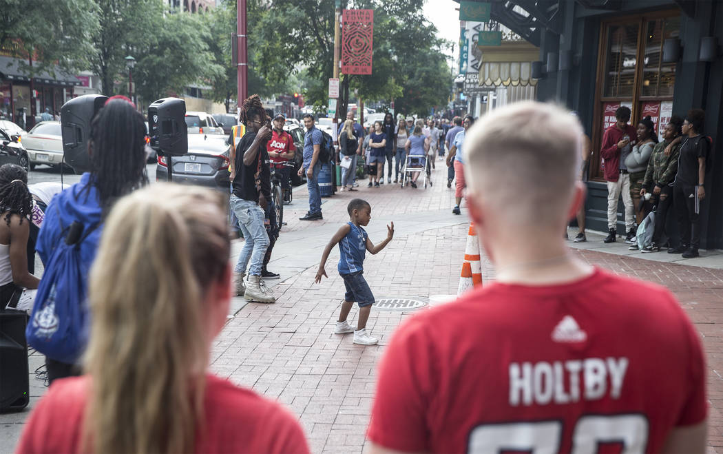 Capitals fans watch a street performer outside Capital One Arena before the start of Game 3 of the NHL Stanley Cup Final against the Golden Knights on Saturday, June 2, 2018, in Washington. Benjam ...
