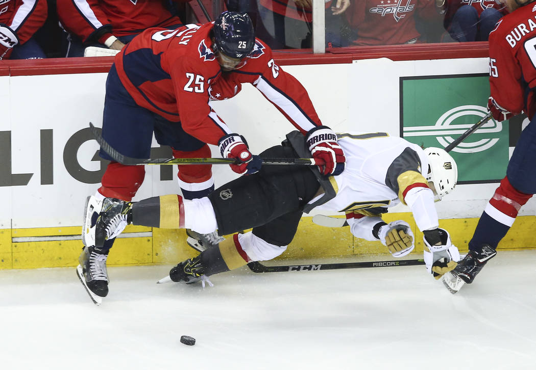 Golden Knights center Cody Eakin (21) gets checked by Washington Capitals right wing Devante Smith-Pelly (25) during the first period of Game 3 of the NHL hockey Stanley Cup Final at Capital One A ...