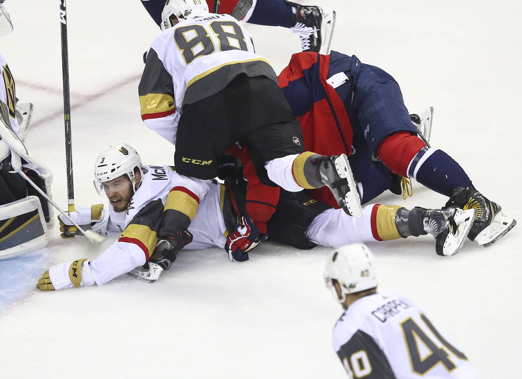 Washington Capitals left wing Alex Ovechkin (8) and Golden Knights defenseman Nate Schmidt (88) fall on top of Golden Knights defenseman Brayden McNabb (3) during the first period of Game 3 of the ...