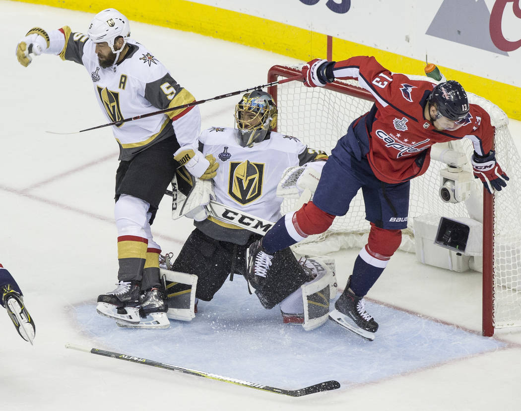 Golden Knights goaltender Marc-Andre Fleury (29) collides with defenseman Deryk Engelland (5) and Capitals left wing Jakub Vrana (13) in the first period during Game 3 of the NHL Stanley Cup Final ...