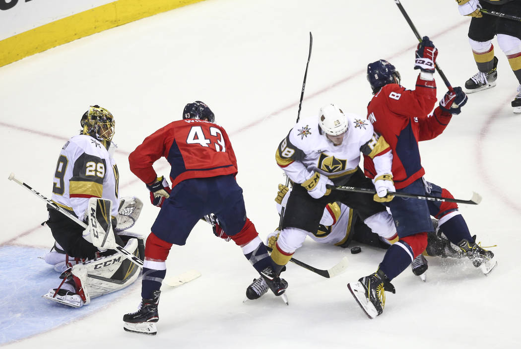Golden Knights defenseman Nate Schmidt (88) and Washington Capitals left wing Alex Ovechkin (8) battle for the puck during the first period of Game 3 of the NHL hockey Stanley Cup Final at Capital ...