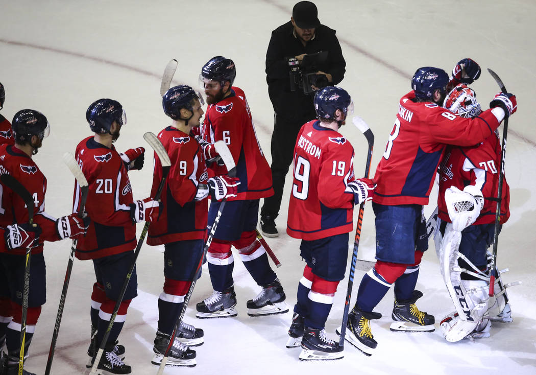 Washington Capitals left wing Alex Ovechkin (8) embraces goaltender Braden Holtby (70) after their win over the Golden Knights in Game 3 of the NHL hockey Stanley Cup Final at Capital One Arena in ...