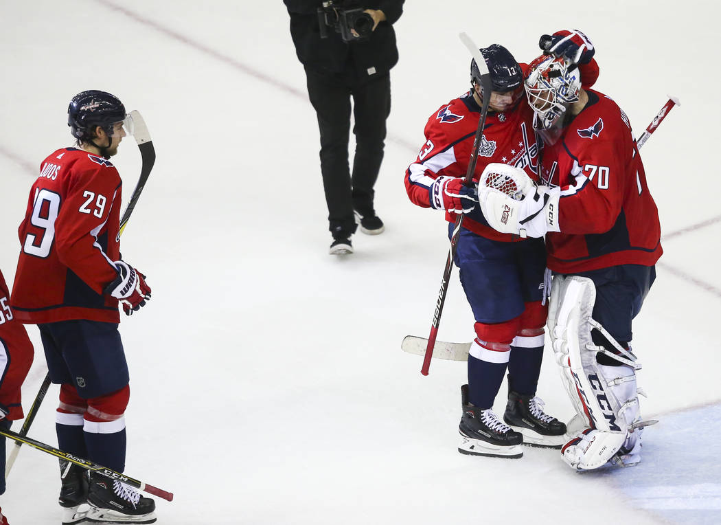 Washington Capitals left wing Jakub Vrana (13) and goaltender Braden Holtby (70) celebrate their win over the Golden Knights in Game 3 of the NHL hockey Stanley Cup Final at Capital One Arena in W ...
