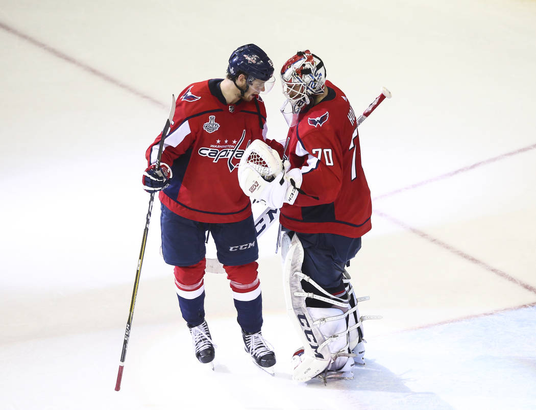 Washington Capitals left wing Andre Burakovsky (65) and goaltender Braden Holtby (70) celebrate their win over the Golden Knights in Game 3 of the NHL hockey Stanley Cup Final at Capital One Arena ...