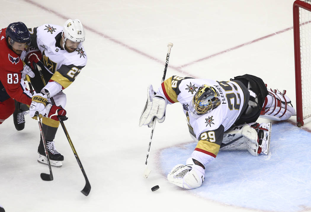 Golden Knights goaltender Marc-Andre Fleury (29) dives for an attempted save in front of Washington Capitals center Jay Beagle (83) and Golden Knights defenseman Shea Theodore (27) during the seco ...