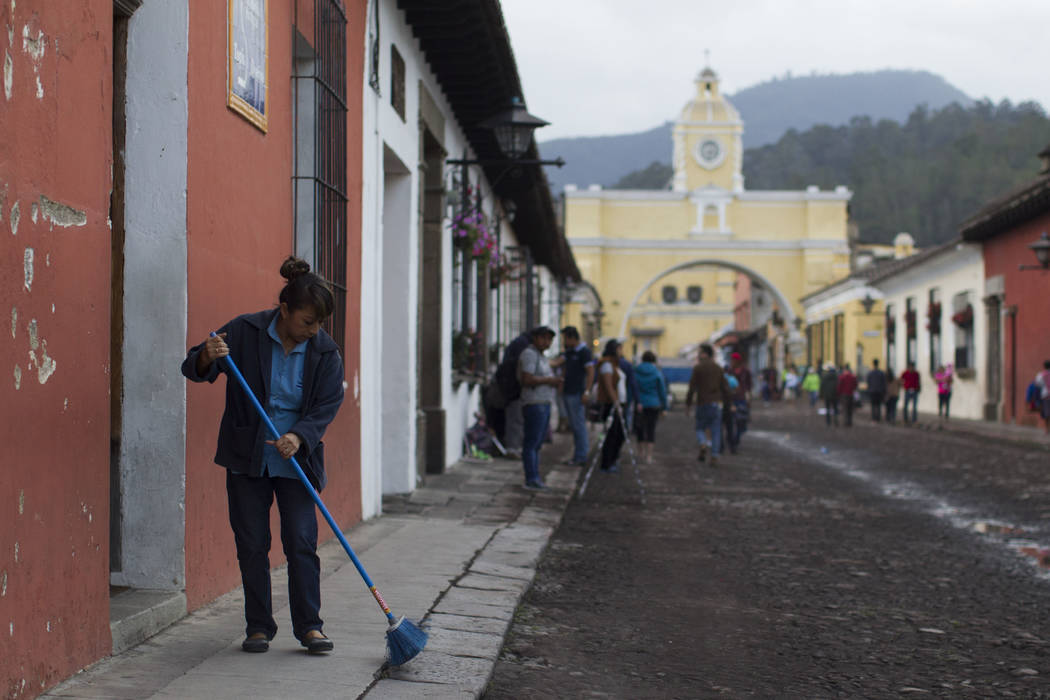 A woman sweeps volcanic ash brought by the Volcan del Fuego, from the sidewalk in Antigua Guatemala, Sunday, June 3, 2018. Volcan del Fuego is one of the most active volcanoes in Central America. ...