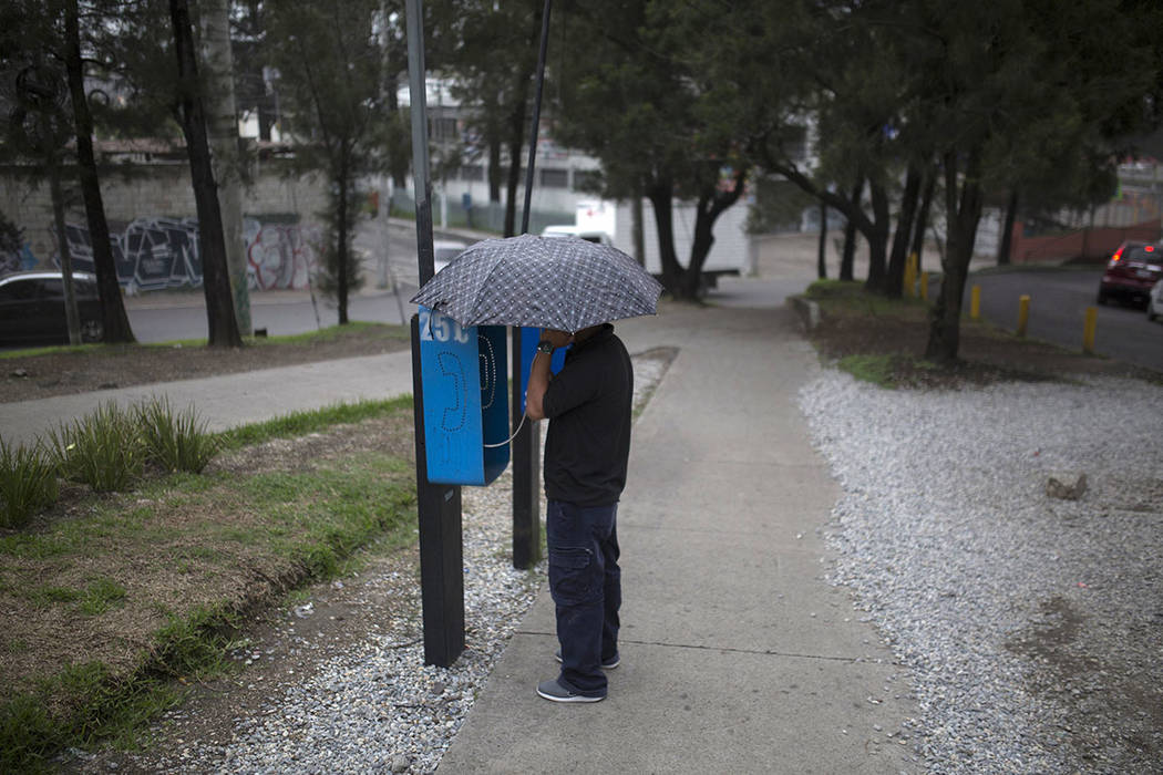 A man using a pay phone protects himself with an umbrella from a light rain of volcanic ash, after the Volcan de Fuego erupted, in Guatemala City, Sunday, June 3, 2018. Volcan del Fuego is one of ...