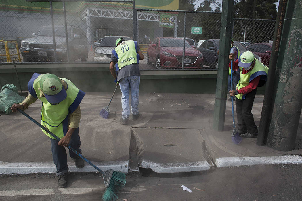 City workers sweep volcanic ash brought by the Volcan del Fuego, in Guatemala City, Sunday, June 3, 2018. Volcan del Fuego is one of the most active volcanoes in Central America. (AP Photo/Luis Soto)
