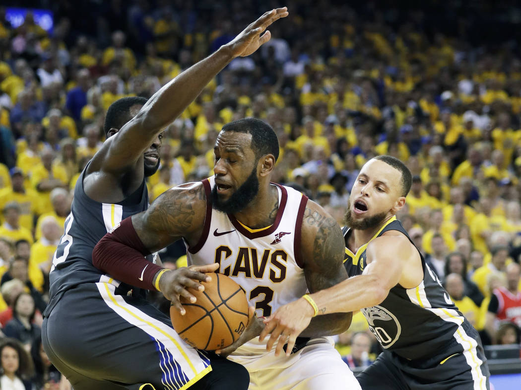 Cleveland Cavaliers forward LeBron James, center, is defended by Golden State Warriors forward Draymond Green, left, and guard Stephen Curry during the second half of Game 2 of basketball's NBA Fi ...