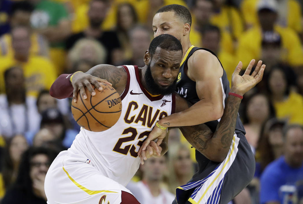 Cleveland Cavaliers forward LeBron James (23) drives against Golden State Warriors guard Stephen Curry during the first half of Game 2 of basketball's NBA Finals in Oakland, Calif., Sunday, June 3 ...