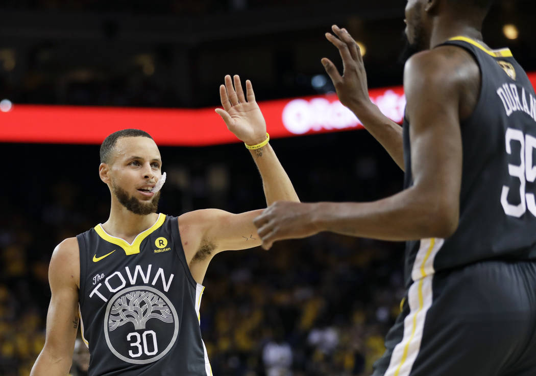Golden State Warriors guard Stephen Curry (30) celebrates with forward Kevin Durant during the first half of Game 2 of basketball's NBA Finals against the Cleveland Cavaliers in Oakland, Calif., S ...