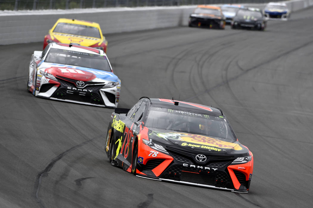 Martin Truex Jr. drives into Turn 1 ahead of Kyle Busch during a NASCAR Cup Series auto race, Sunday, June 3, 2018, in Long Pond, Pa. Truex won the race. (AP Photo/Derik Hamilton)