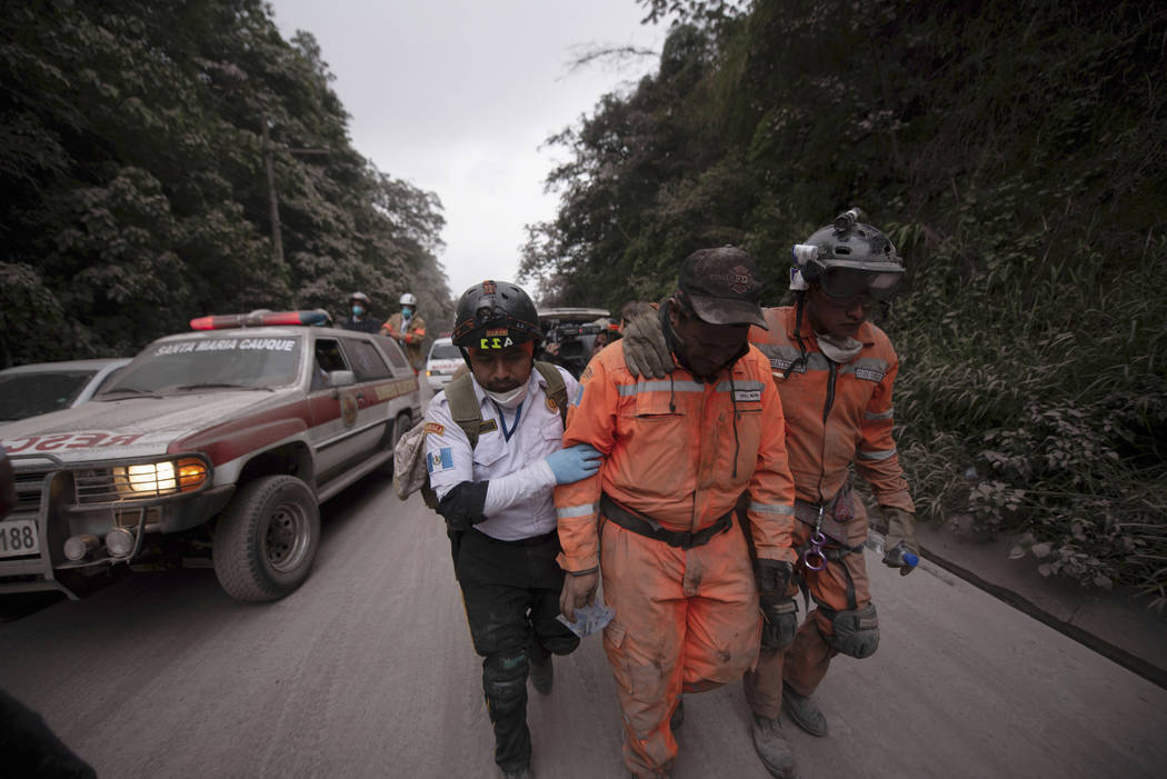 Firefighters leave the evacuation area near Volcan de Fuego, or Volcano of Fire, in El Rodeo, Guatemala, Sunday, June 3, 2018. One of Central America's most active volcanos erupted in fiery explos ...