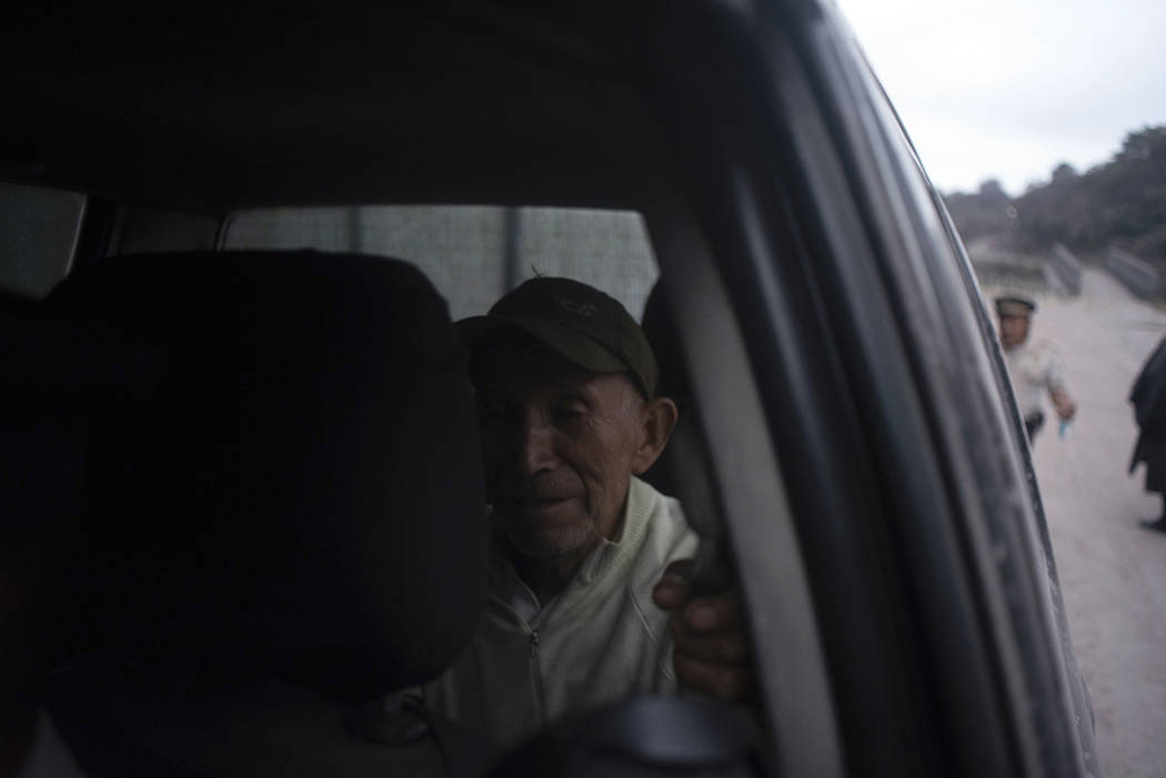 An evacuated man waits to be transferred while sitting in a police car near Volcan de Fuego, or Volcano of Fire, in El Rodeo, Guatemala, Sunday, June 3, 2018. One of Central America's most active ...