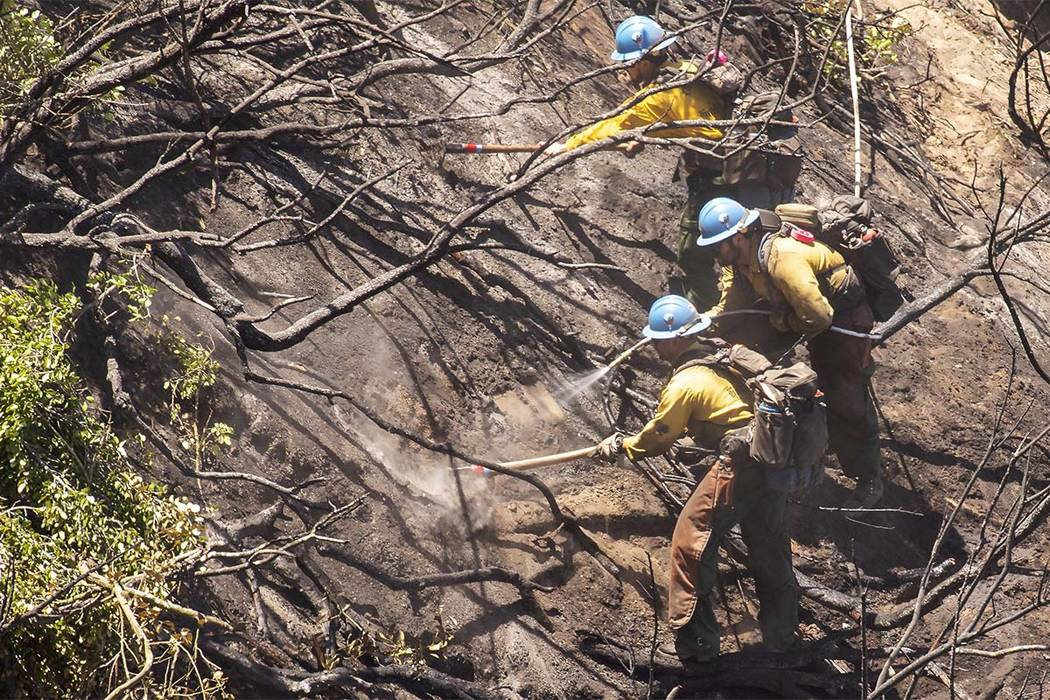 Fire crews put out hot spots at a brush fire in Wood Canyon in the hills below Soka University in Aliso Viejo, Calif., Sunday, June 3, 2018. The Orange County Fire Authority estimates the fire bur ...