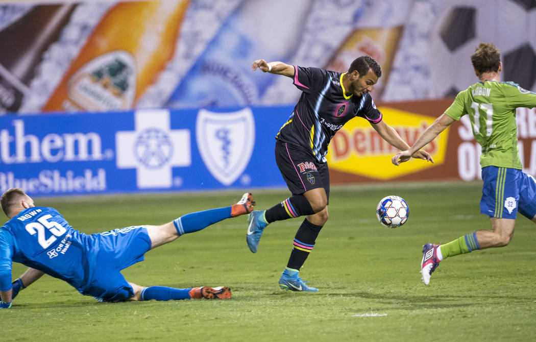 Las Vegas Lights FC forward Sammy Ochoa, center, breaks past Seattle Sounders FC 2 goalie Calle Brown (25) and Sounders midfielder Francisco Narbon (77) for a goal during the first half of a Unite ...