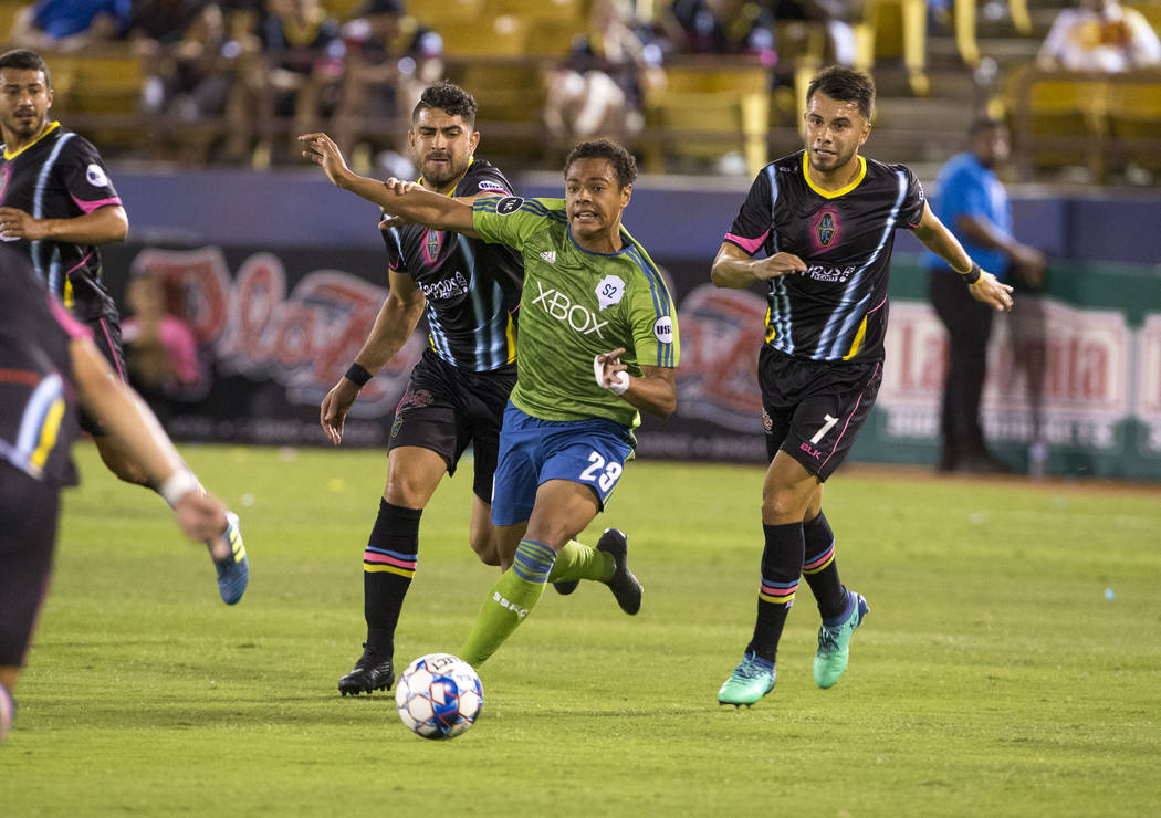Seattle Sounders FC 2 midfielder Henry Wingo (23), center, breaks through Las Vegas Lights FC defender Marco Cesar Jaime Jr. (6), left, and midfielder Carlos Alvarez (7) during the first half of a ...