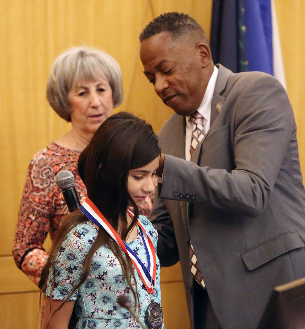 Aalyiah Inghram, 10, who was shot while protecting her 18-month-old brother and 4-year-old cousin during a shootout on May 8, 2018, receives medal of courage from Clark County Commissioner Lawrenc ...