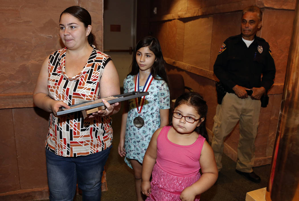 Aalyiah Inghram, 10, center, who was shot while protecting her 18-month-old brother and 4-year-old cousin during a shootout on May 8, 2018, leaves the Clark County Commission chambers with her mot ...