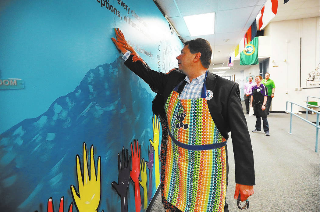 Superintendent Pat Skorkowsky, who is retiring, paints a handprint on a mural dedicated to him during a surprise party at C.C. Ronnow Elementary School in Las Vegas on Friday, May 4, 2018. Andrea ...