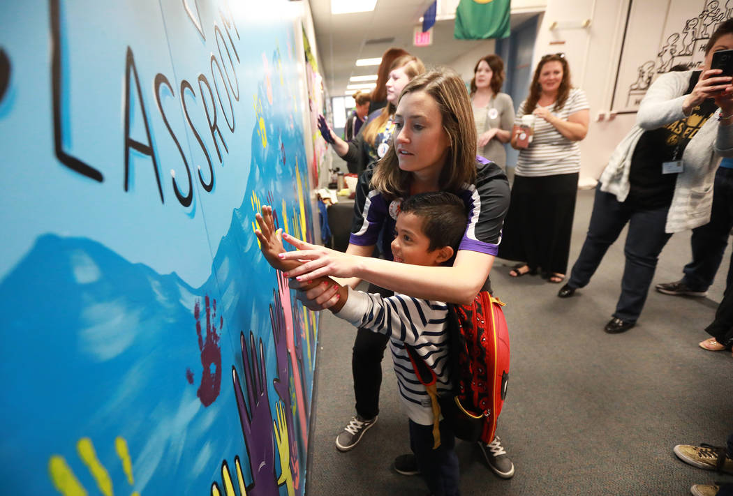 Ginny Kirkendall, a learning strategist, helps Omar Rodriguez, 5, paint a handprint on a mural dedicated to superintendent Pat Skorkowsky, who is retiring, at C.C. Ronnow Elementary School in Las ...