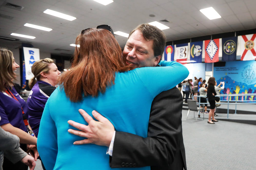 Superintendent Pat Skorkowsky, who is retiring, embraces Brianna Lindberg, a second grade teacher, during a surprise party at C.C. Ronnow Elementary School in Las Vegas on Friday, May 4, 2018. And ...