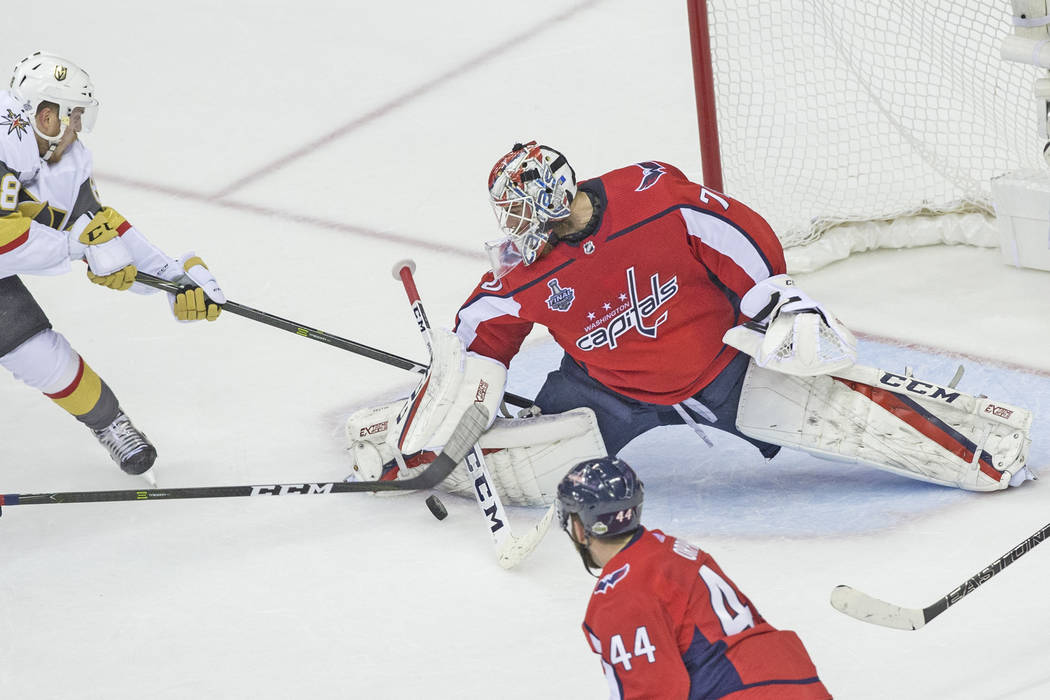 Capitals goaltender Braden Holtby (70) makes a second-period save against Golden Knights defenseman Nate Schmidt (88) during Game 4 of the NHL Stanley Cup Final on Monday, June 4, 2018, at Capital ...