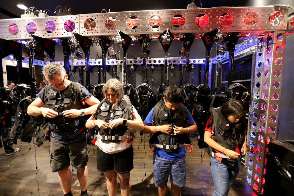 Thomas Bladh and Eva Zander of Sweden, left, and Thirdy and Chloe Aldevera of the Philippines attach their vests at The VOID immersive virtual reality attraction at Grand Canal Shoppes in The Vene ...