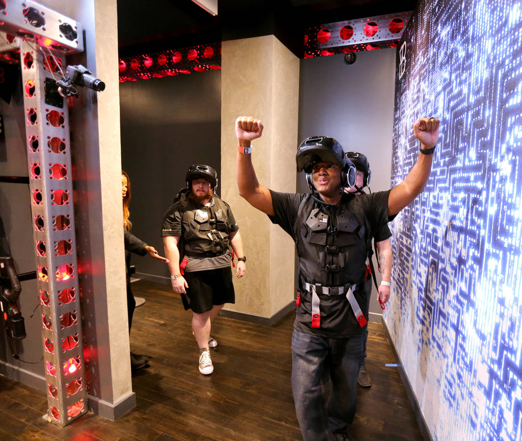 Dwayne Gordon, front, followed by James Koch, right, and Sean Brown, all of Las Vegas, after an adventure at The VOID immersive virtual reality attraction at Grand Canal Shoppes in The Venetian Tu ...