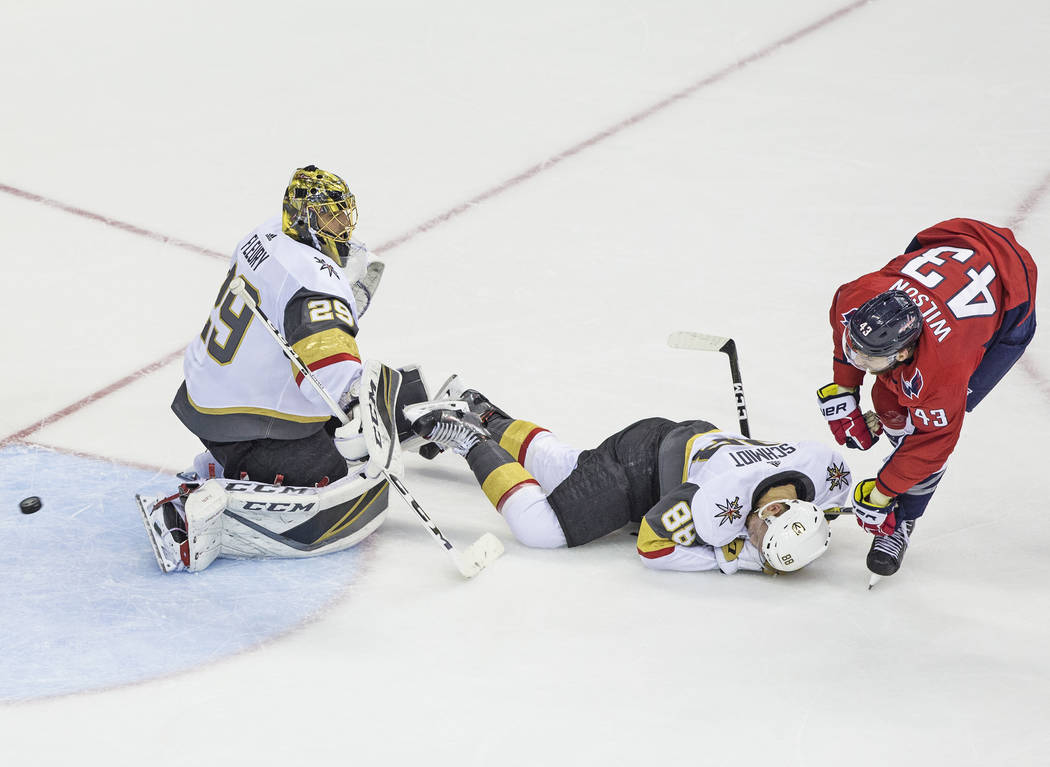 Golden Knights goaltender Marc-Andre Fleury (29) and defenseman Nate Schmidt (88) team up to make a second period save against Capitals right wing Tom Wilson (43) during Game 4 of the NHL Stanley ...
