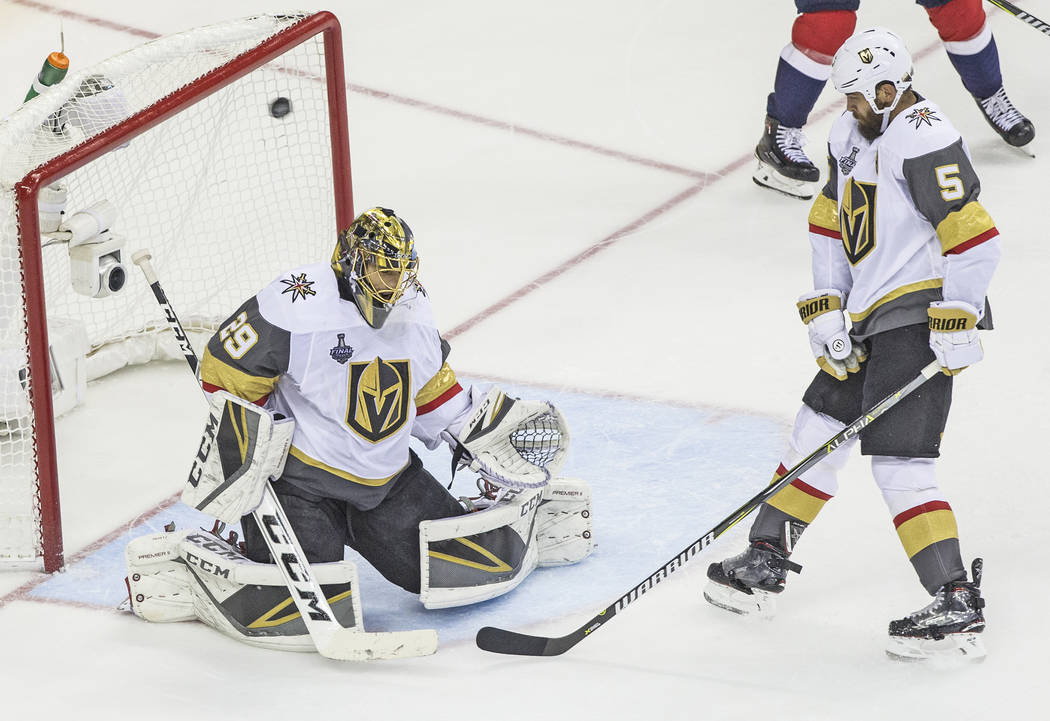 Golden Knights goaltender Marc-Andre Fleury (29) and defenseman Deryk Engelland (5) give up a second- period goal to Capitals defenseman John Carlson (74) during Game 4 of the NHL Stanley Cup Fina ...