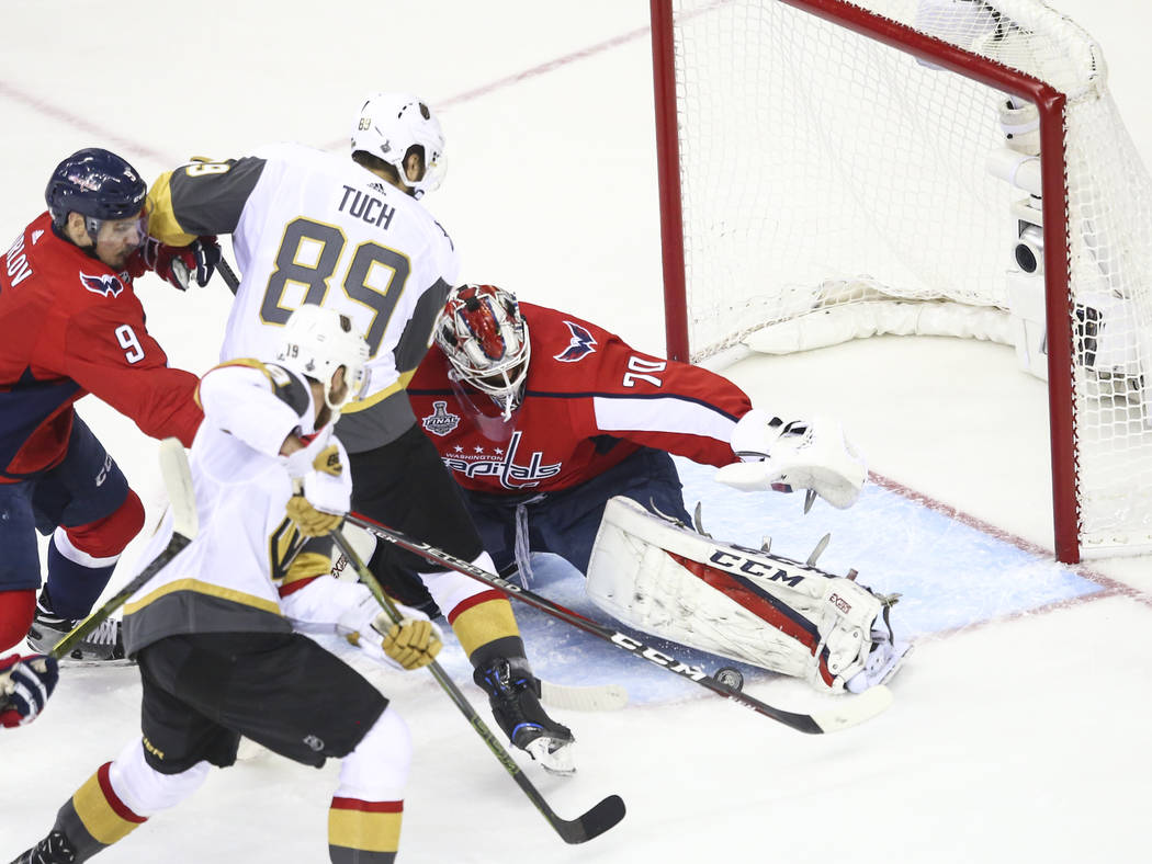 Golden Knights right wing Alex Tuch (89) tries to get the puck in past Washington Capitals goaltender Braden Holtby (70) during the first period of Game 4 of the Stanley Cup Final at Capital One A ...