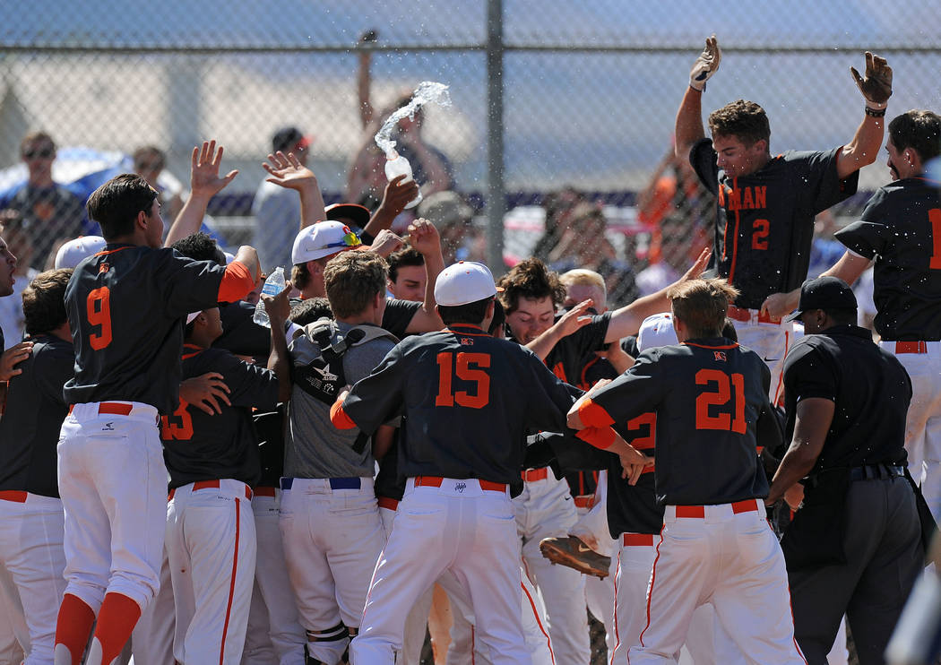 Bishop Gorman's Cadyn Grenier, right, jumps into a pile of players waiting at home plate after he hit a walk-off home run in the ninth inning of the NIAA Division I State championship baseball gam ...