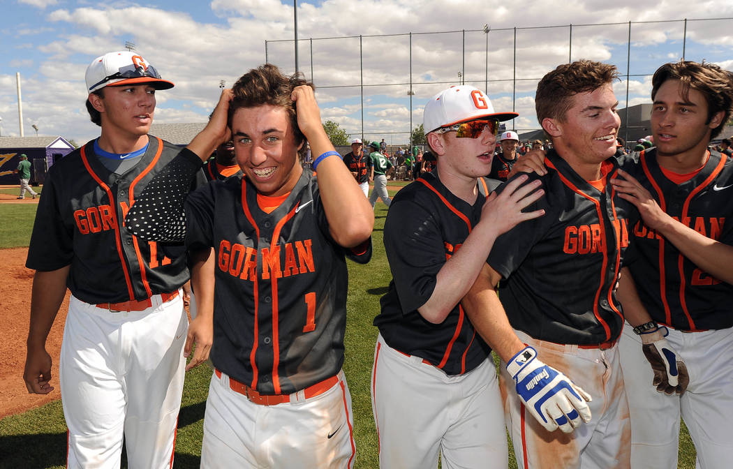 Bishop Gorman players celebrate with Cadyn Grenier, right, blue batting gloves, after he hit a walk-off home run in the ninth inning of the NIAA Division I State championship baseball game against ...