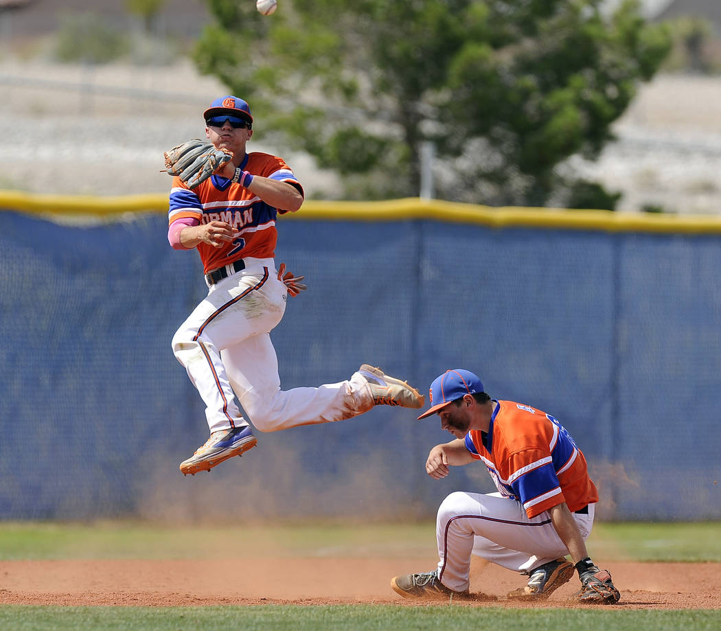 Bishop Gorman shortstop Cadyn Grenier makes an acrobatic throw over third baseman Beau Capanna in attempt to throw out Centennial's Josh McKibbinn in the sixth inning of the Sunset Region Champion ...