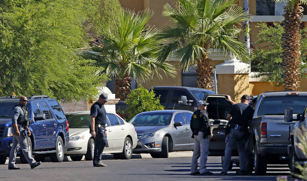 Police surround a hotel where a suspect wanted in multiple killings was staying Monday, June 4, 2018, in Scottsdale, Ariz. According to police, the suspect killed himself as police closed in on th ...