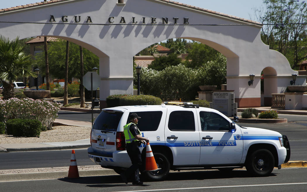 Police block off access to a business plaza as they surround a hotel where a suspect wanted in several killings was staying Monday, June 4, 2018, in Scottsdale, Ariz. According to police, the susp ...