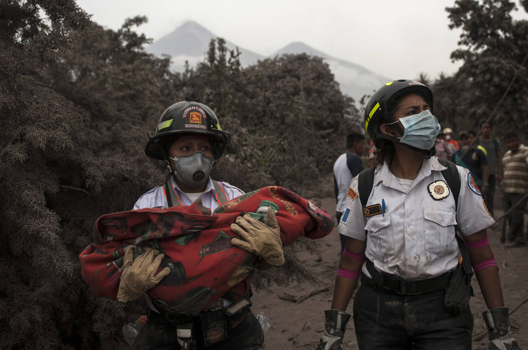 A firefighter carries the body of a child recovered near the Volcan de Fuego, which means in Spanish Volcano of Fire, in Escuintla, Guatemala, Monday, June 4, 2018. A fiery volcanic eruption in so ...