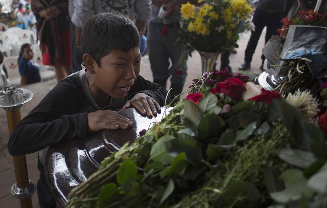 A youth cries over the coffin of Nery Otoniel Gomez Rivas, 17, whose body was pulled from the volcanic ash during the eruption of the Volcan de Fuego, which in Spanish means Volcano of Fire, durin ...