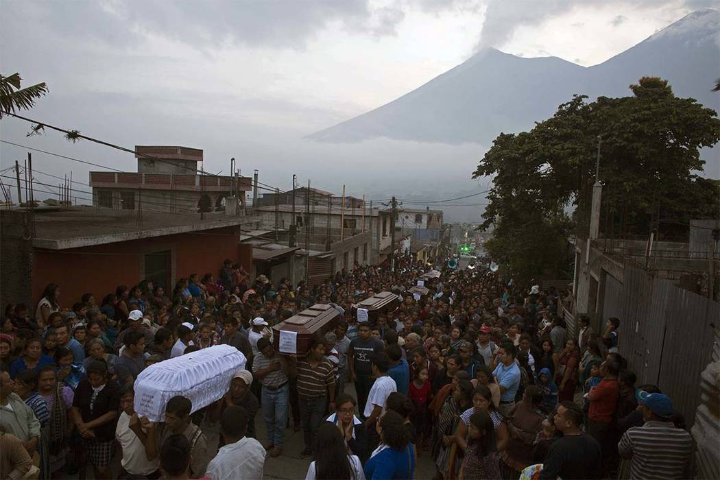 People carry the coffins of seven people who died during the eruption of the Volcan de Fuego, which in Spanish means Volcano of Fire, in the background, to the cemetery in San Juan Alotenango, Gua ...