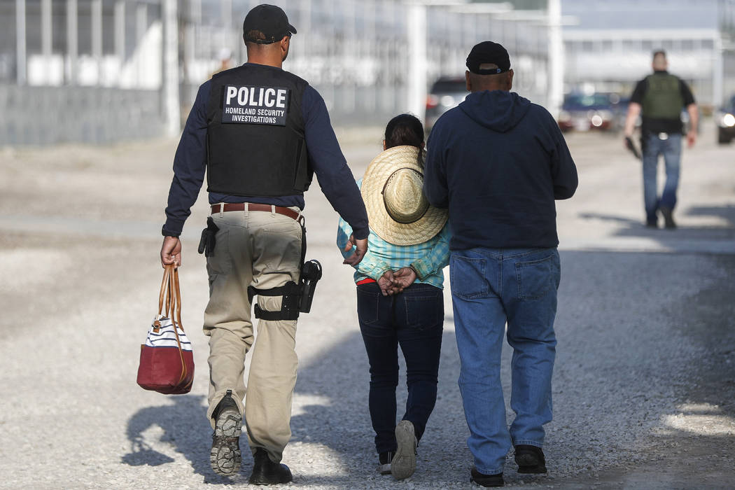 Government agents take a woman suspected of living in the country illegally into custody during an immigration sting at Corso's Flower and Garden Center in Castalia, Ohio, Tuesday, June 5, 2018. T ...