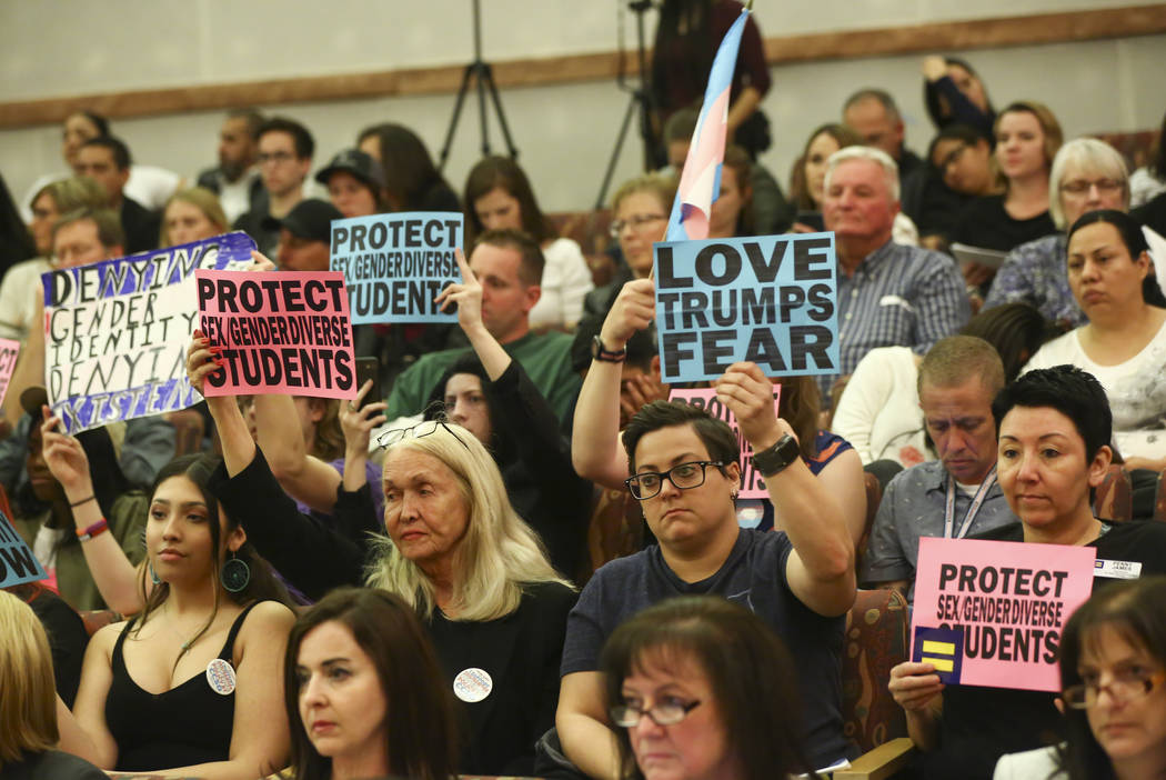 Attendees hold up signs in support of a gender-diverse policy for the school district during a Clark County School District Board of Trustees meeting at the County Government Center in Las Vegas o ...