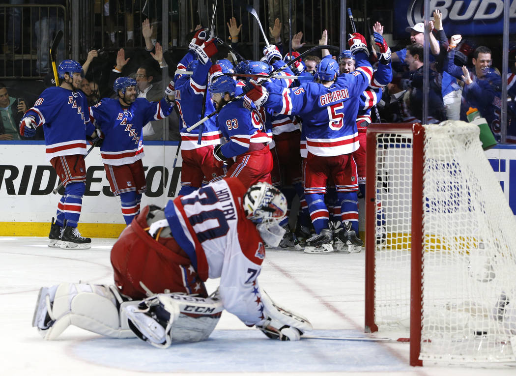 FILE - In this May 13, 2015, file photo, the New York Rangers celebrate the game winning goal by center Derek Stepan (21) against the Washington Capitals as Capitals goalie Braden Holtby looks at ...