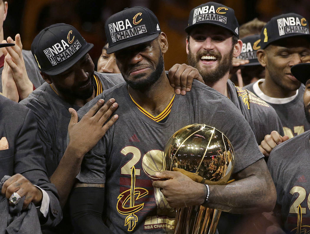 FILE - In this June 19, 2016, file photo, Cleveland Cavaliers forward LeBron James, center, celebrates with teammates, including Kevin Love, third from left, after they won Game 7 of basketball's ...