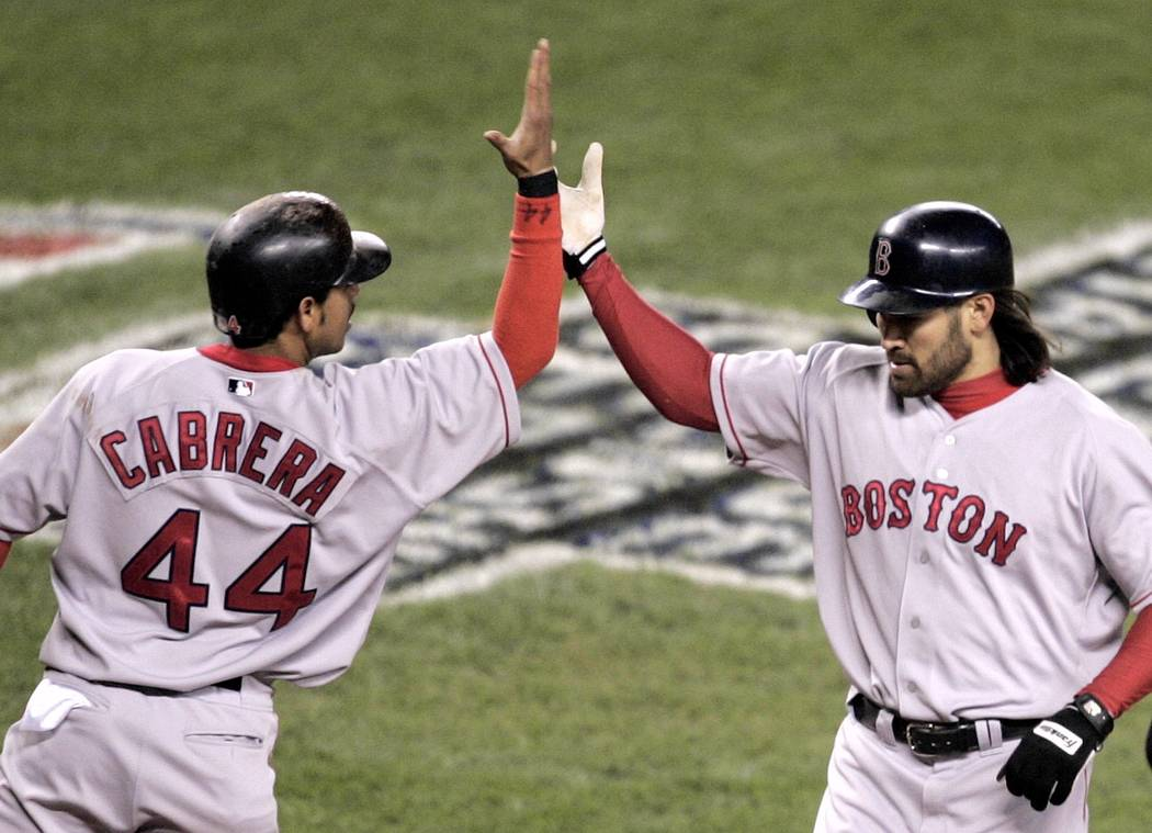 Boston Red Sox' Johnny Damon, right, high-fives with Orlando Cabrera who scored on his two-run, fourth- inning home run against the New York Yankees in game 7 of the ALCS in New York Wednesday, Oc ...